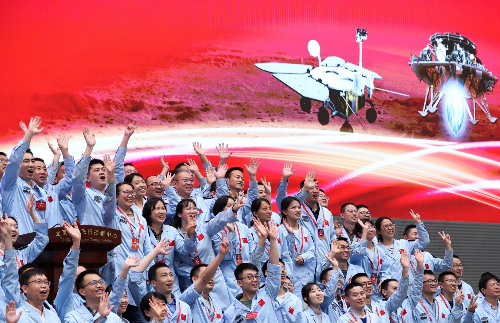 5月15日,航天科研人員在北京航天飛行控制中心指揮大廳慶祝我國首次火星探測任務着陸火星成功。新華社