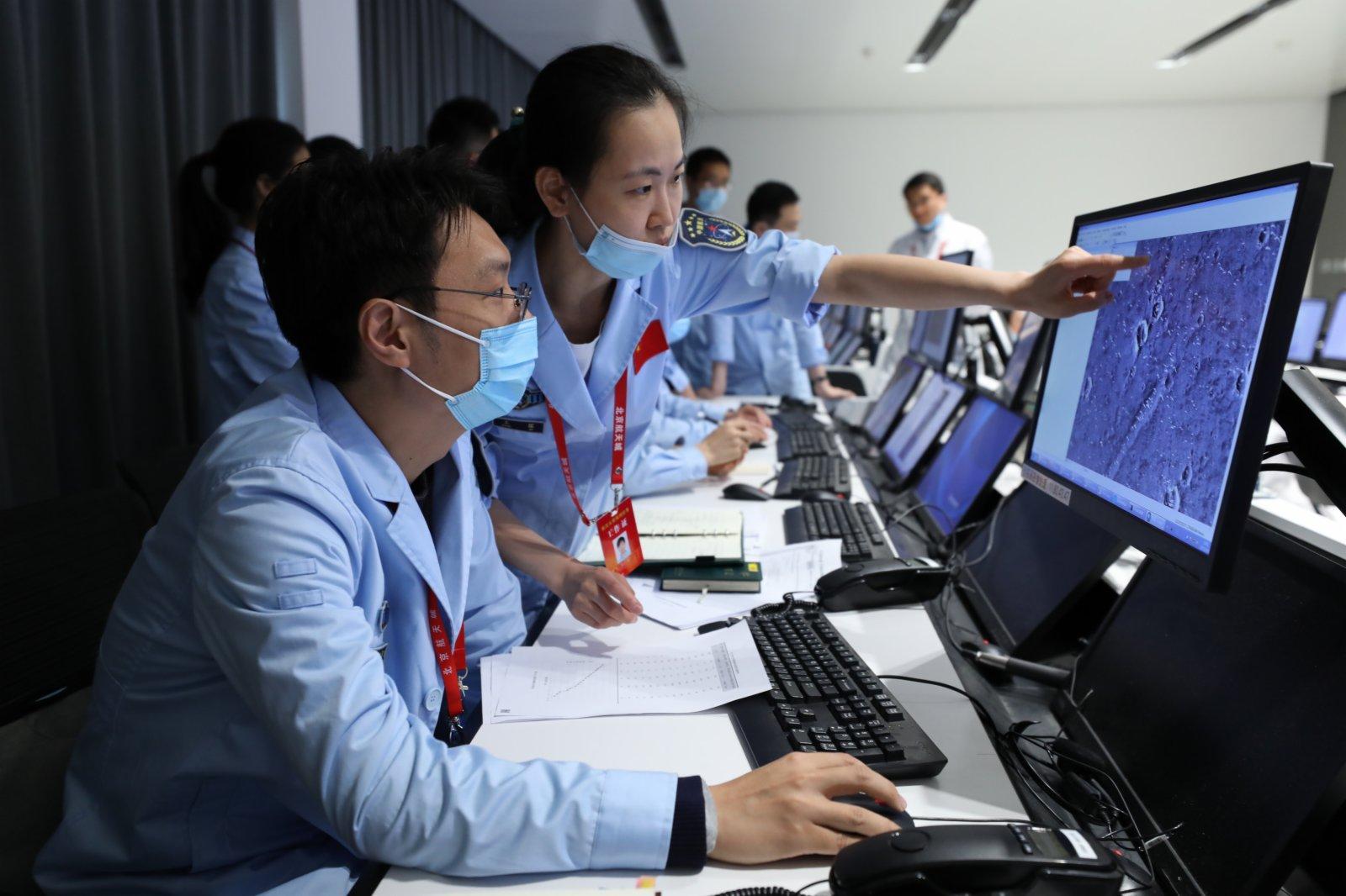 5月15日,航天科研人員在北京航天飛行控制中心監測「祝融號」火星車工作情況,研究傳回的火星地面高清圖片。新華社