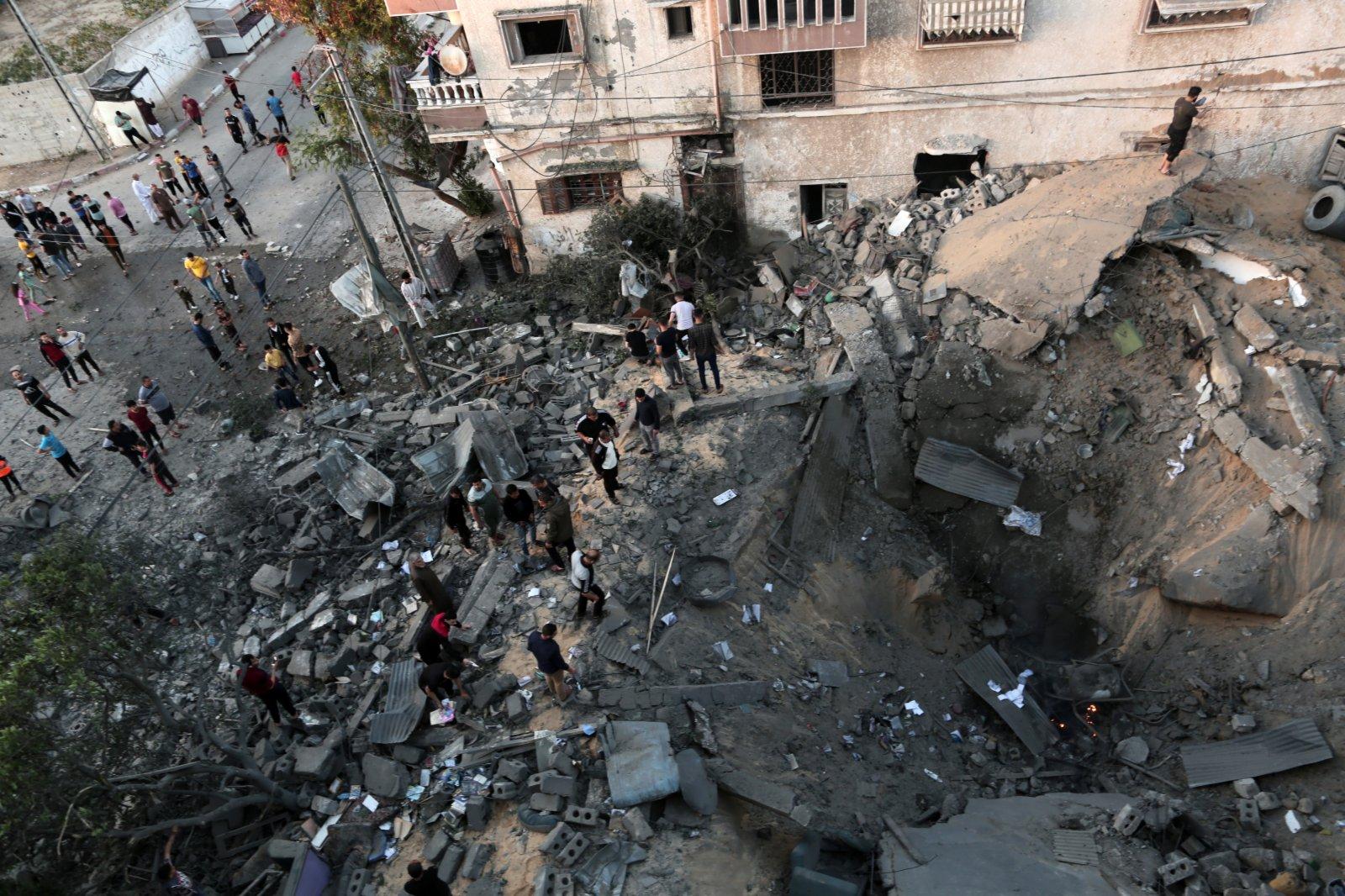 5月14日,巴勒斯坦人在加沙地帶城市汗尤尼斯查看被以軍空襲摧毀的一處房屋。