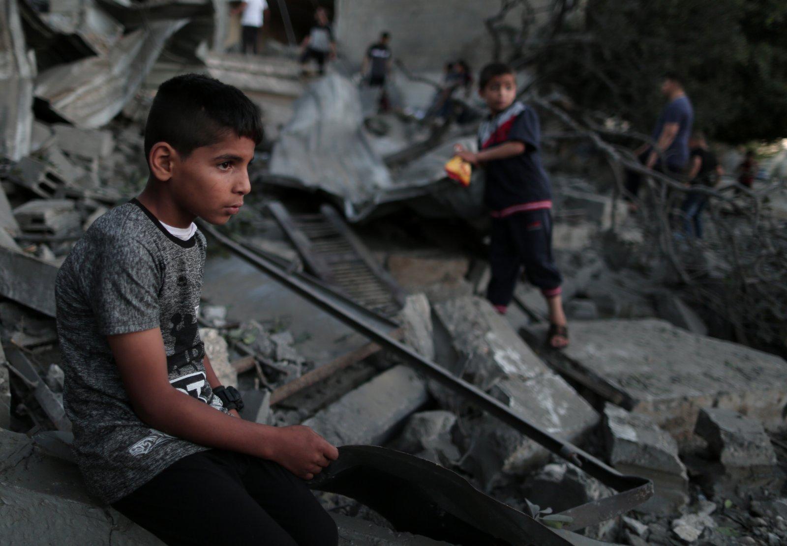 5月14日,在加沙地帶城市汗尤尼斯,巴勒斯坦兒童坐在被以軍空襲摧毀的一處房屋廢墟上。