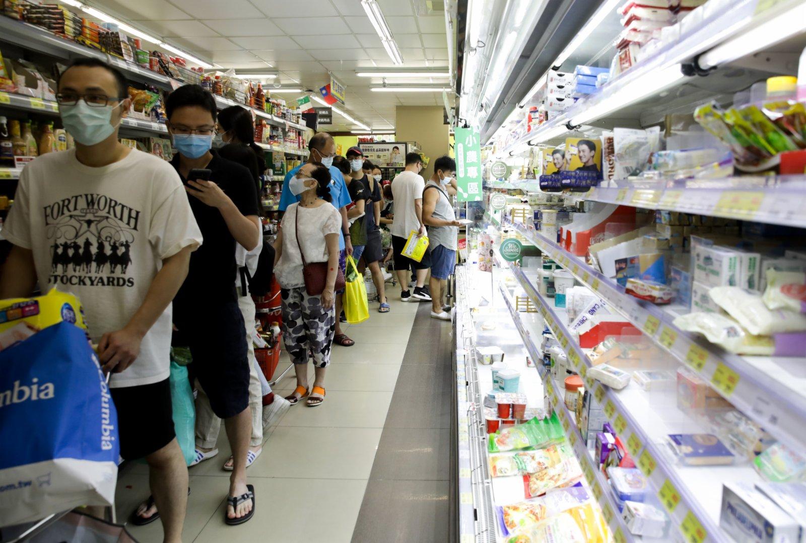 5月15日,台北市許多賣場開始出現民眾搶購的人潮;在商場內,防疫用品如酒精、口罩;衛生紙、泡麵、餅乾、水餃、罐頭等民生用品,瞬間成為民眾選購的熱門商品,貨架上商品,陸續淨空。(彭博社)