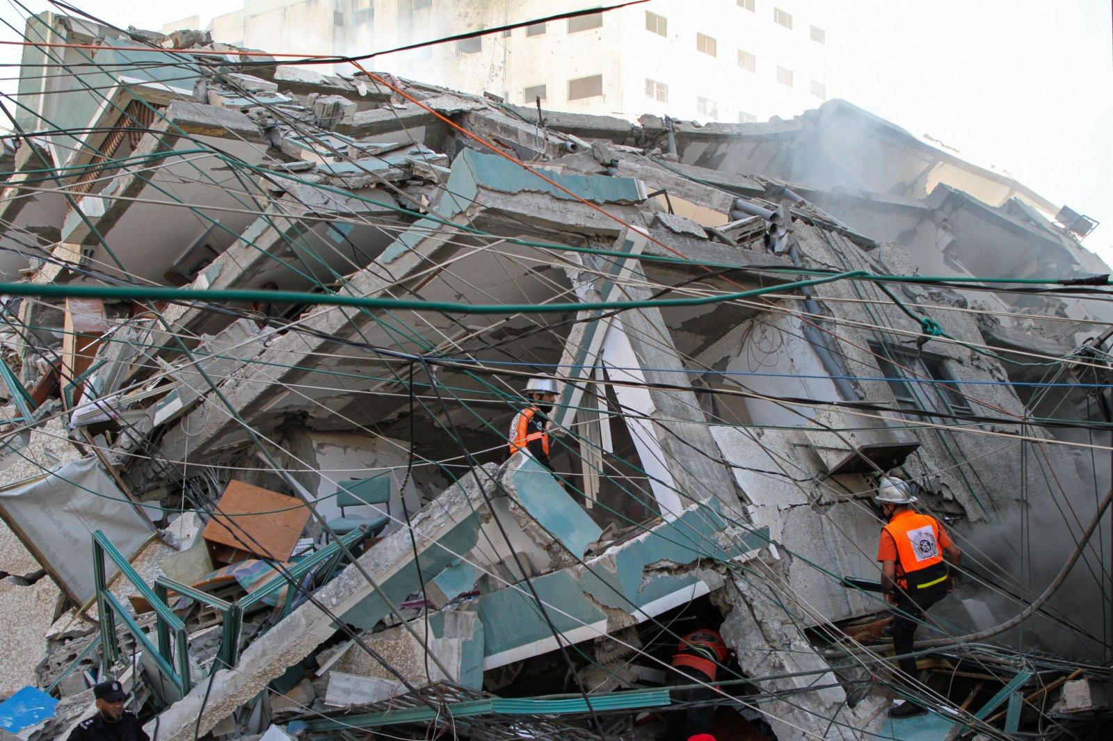 5月15日,巴勒斯坦人查看被以軍空襲過後的位於加沙地帶的一棟多家媒體所在大樓。(新華社)