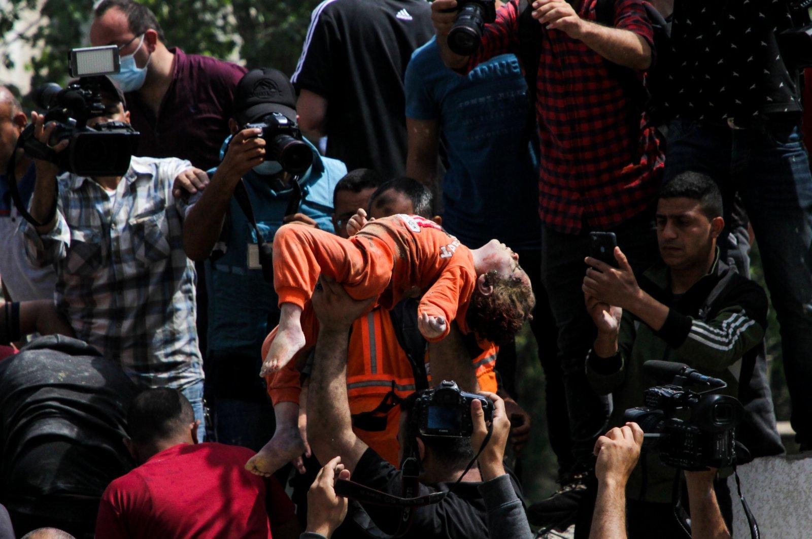 5月16日,巴勒斯坦民防人員從加沙城被炸住宅樓的廢墟中救出一名兒童。(新華社)