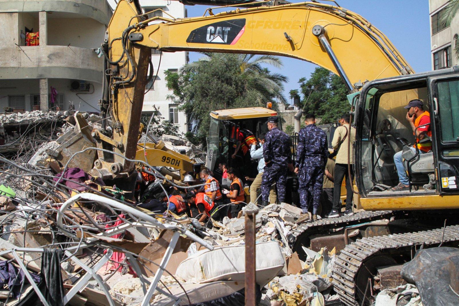 5月16日,巴勒斯坦民防人員在加沙城被炸住宅樓的廢墟中進行搜救。(新華社)