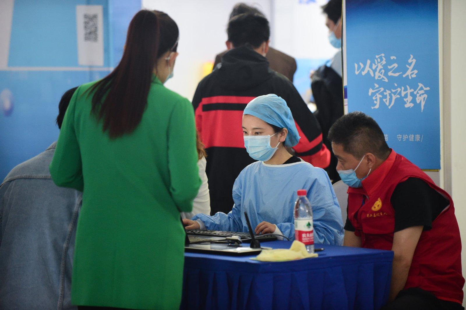 5月16日,在合肥市蜀山區奧體中心方艙接種點,醫務人員(右二)為接種新冠疫苗的市民登記信息。(新華社)