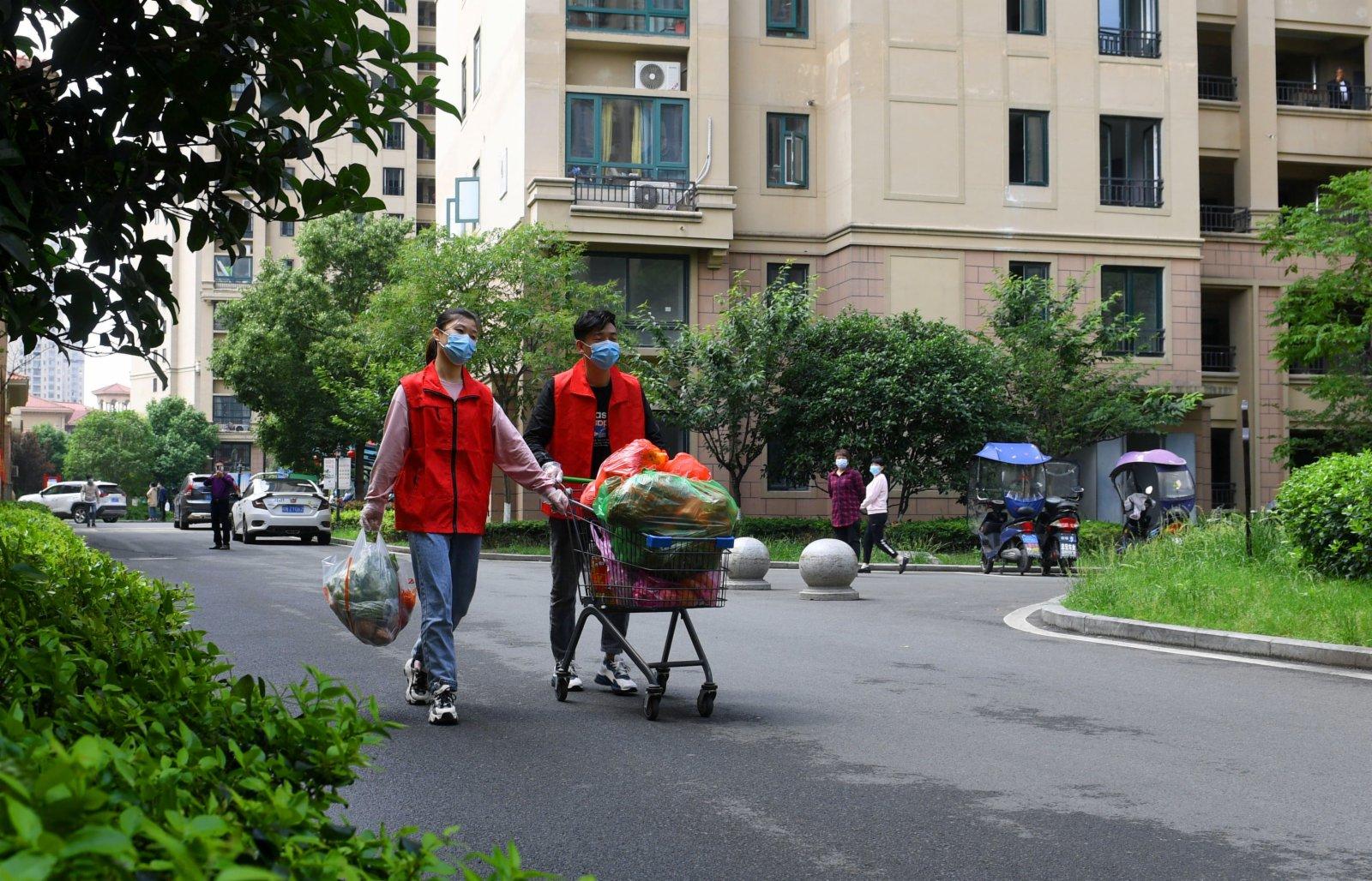 5月17日,兩名志願者為居住在封閉樓棟裡的居民運送生活用品。(新華社)
