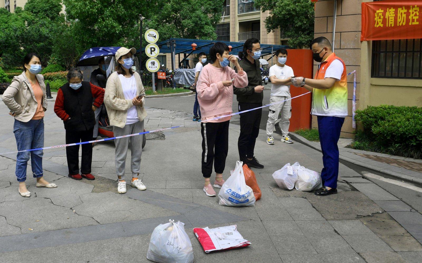 5月17日,志願者核對居民購買物品的清單以便分發。(新華社)