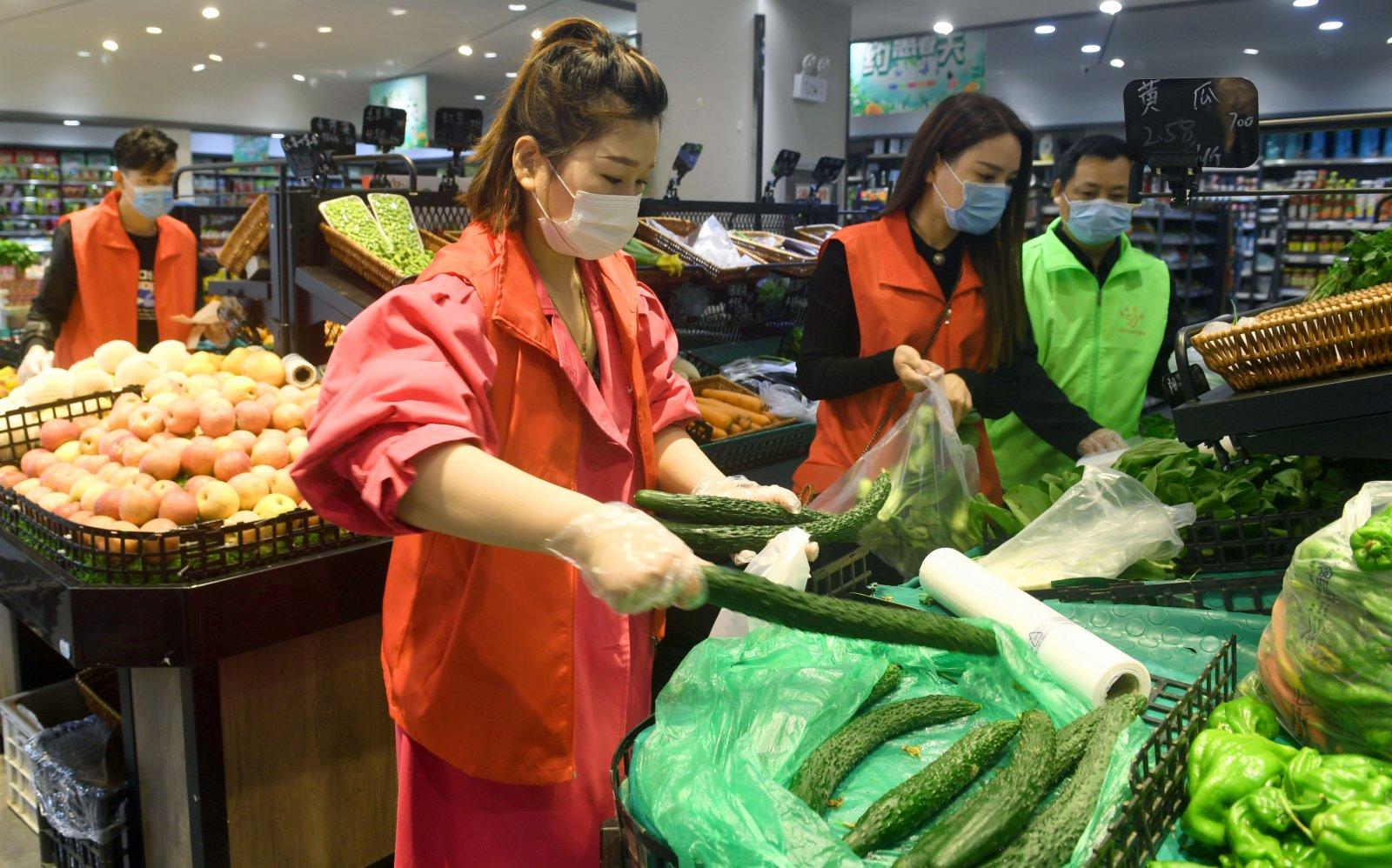 5月17日,志願者在超市為六安市裕安區的居民代買蔬菜。(新華社)