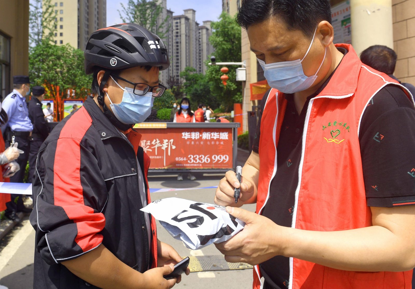 5月17日,六安愛心車隊的志願者張恩權(右)為居民代收快遞。(新華社)