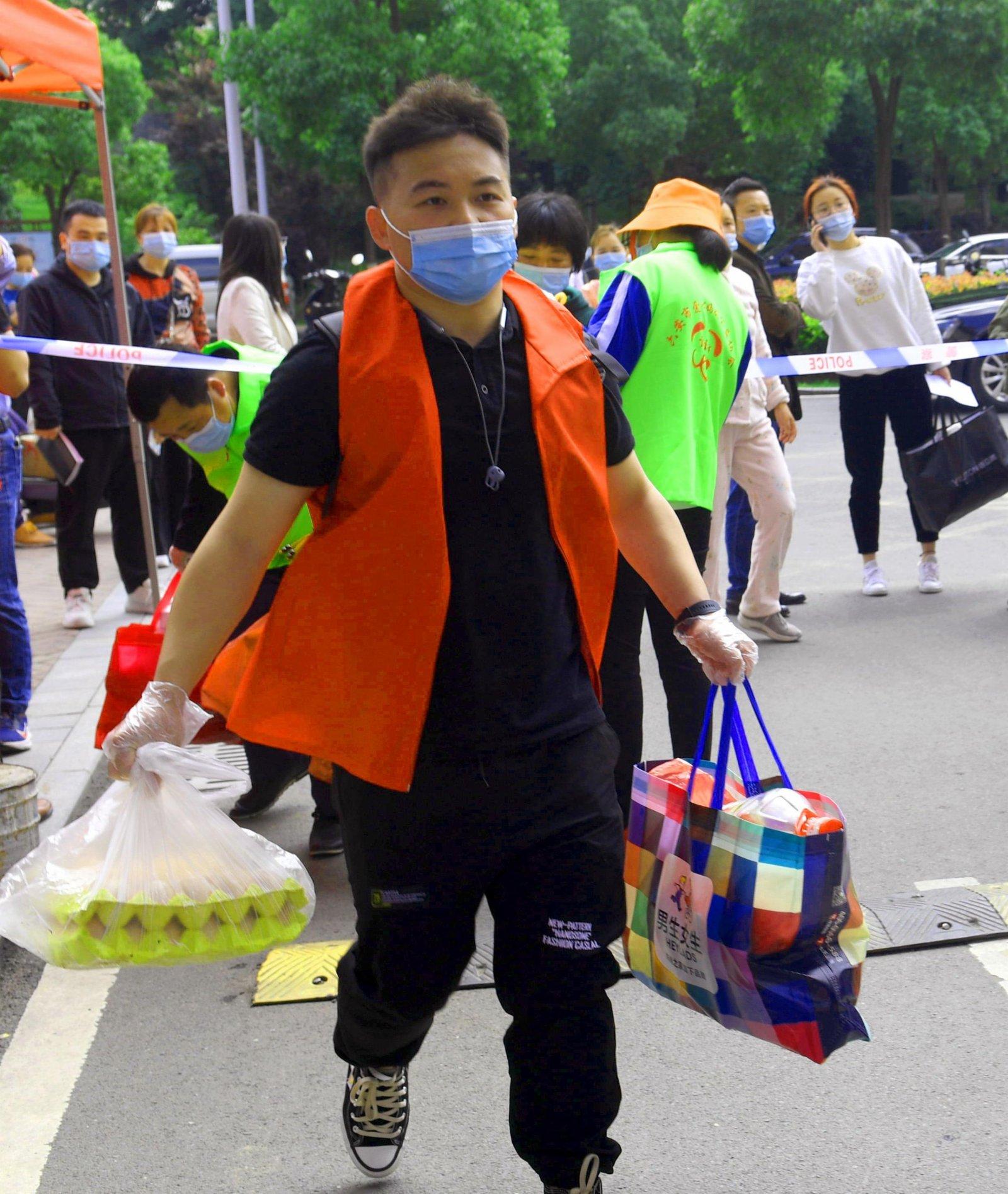 5月17日,一名志願者為居民代購生活用品。(新華社)