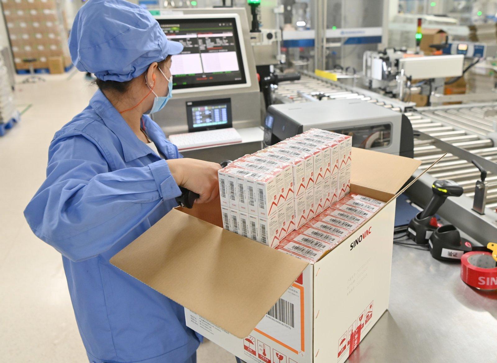 日內瓦當地時間6月1日,世界衞生組織宣布,由中國北京科興中維生物技術有限公司研發的新冠滅活疫苗「克爾來福」正式通過世衞組織緊急使用認證。圖為北京時間6月1日,位於北京市大興區的北京科興中維生物技術有限公司內,工人在新冠滅活疫苗包裝生產線上進行開箱登記掃描作業。(中新社)