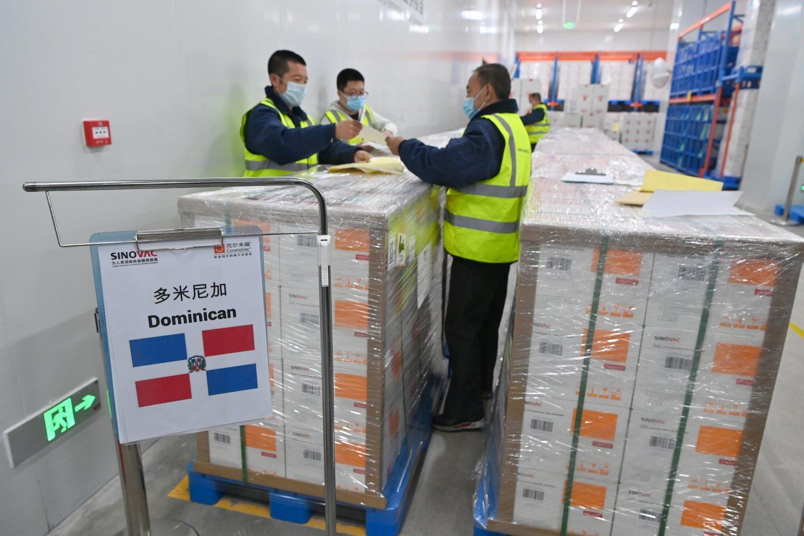 6月1日,中國北京科興中維生物技術有限公司生產的新冠疫苗從該公司位於北京市大興區的廠區倉庫出庫,即日運往多米尼加共和國。圖為工人在疫苗出庫前在外包裝上粘貼相關信息標識。 (中新社)