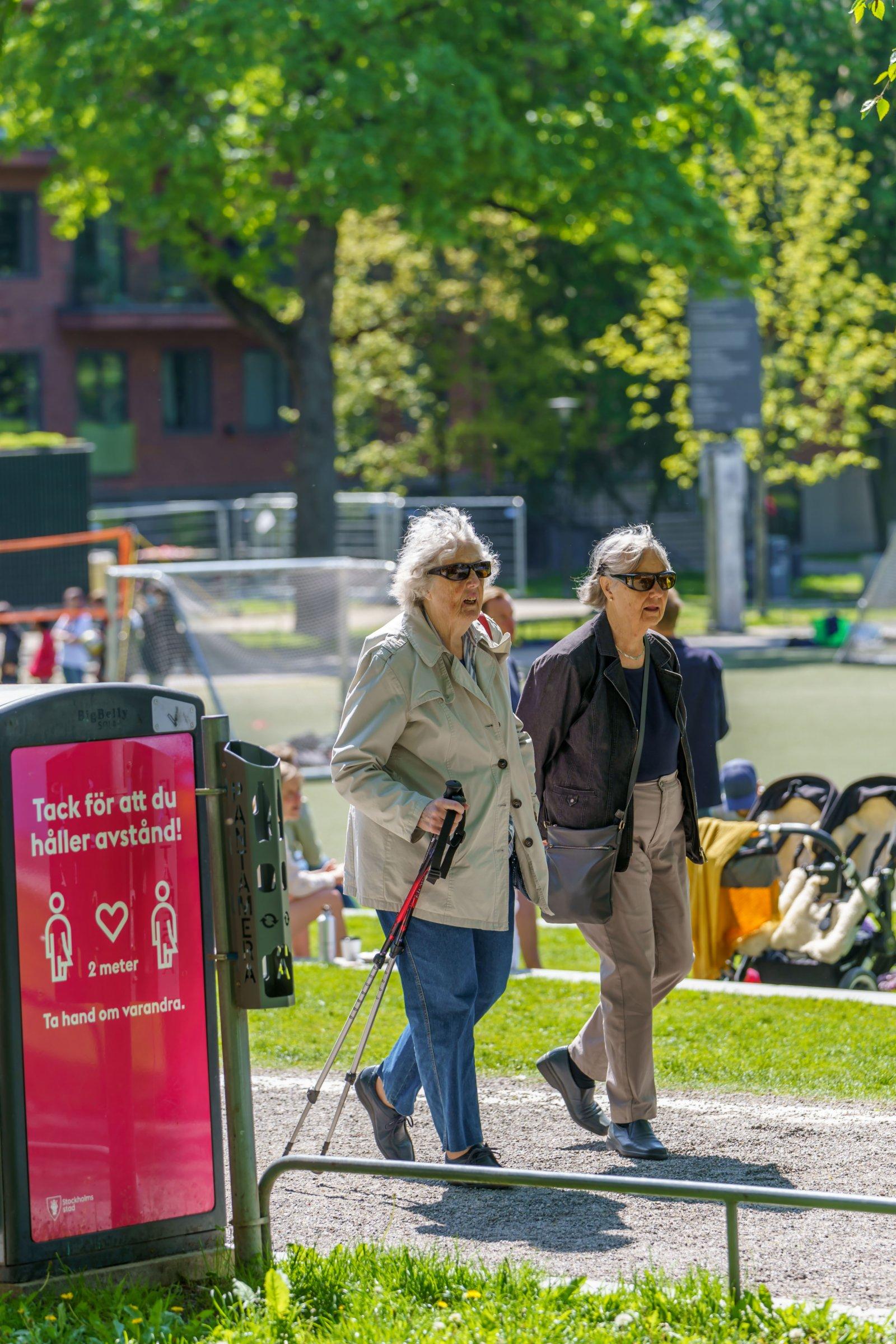 6月1日,行人在瑞典斯德哥爾摩經過一處提醒人們保持社交距離的標識。(新華社)