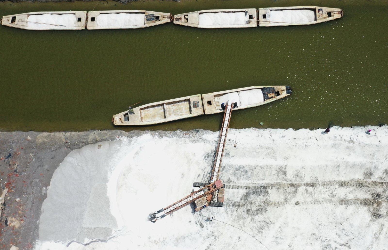 6月5日,南堡鹽場的工人將收穫的春鹽裝船(無人機照片)。