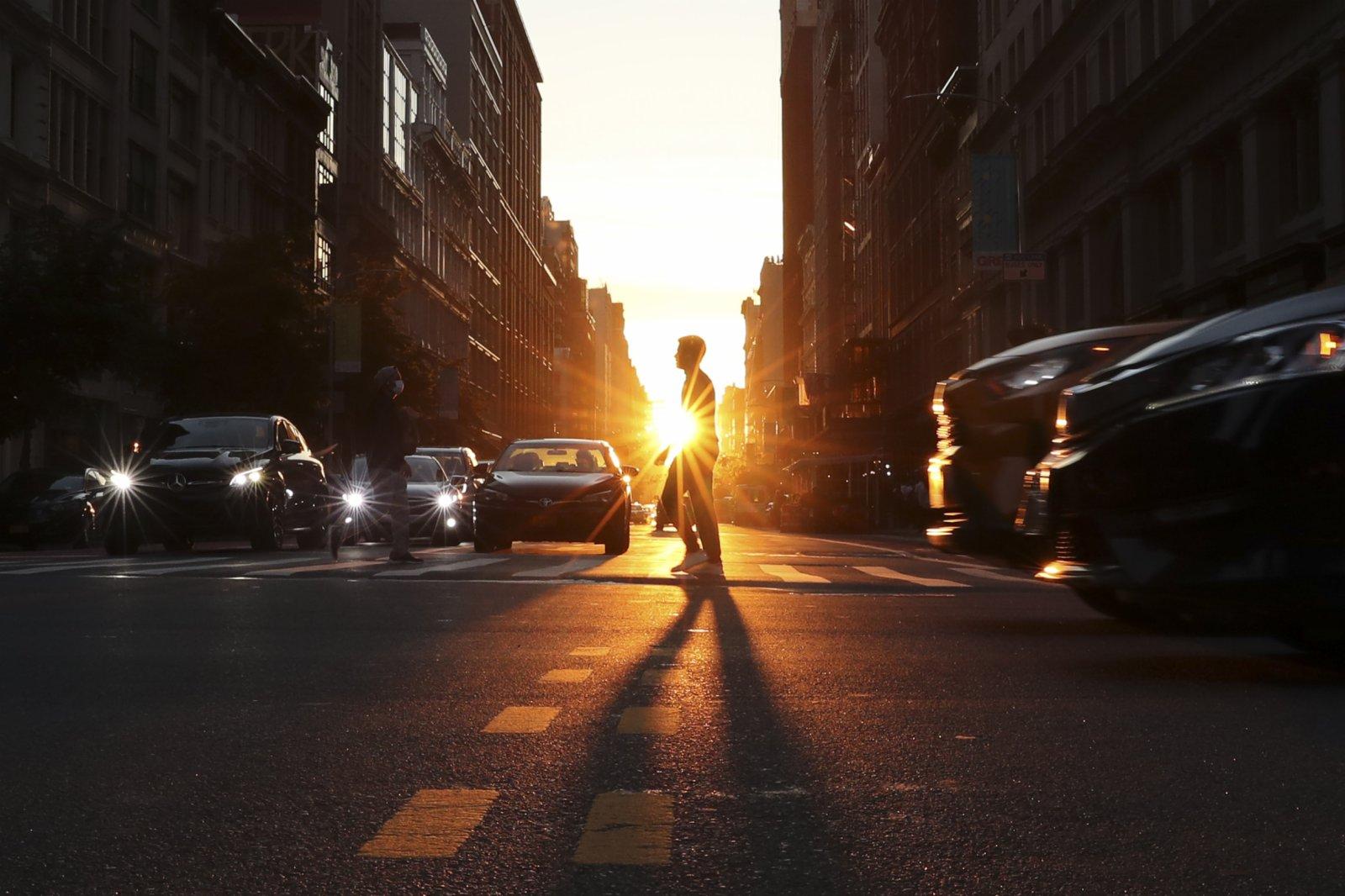 當地時間4日傍晚,接近地平線的太陽出現在紐約曼哈頓東西向街道盡頭,陽光在此刻貫穿整條街道照射在紐約客的身上。