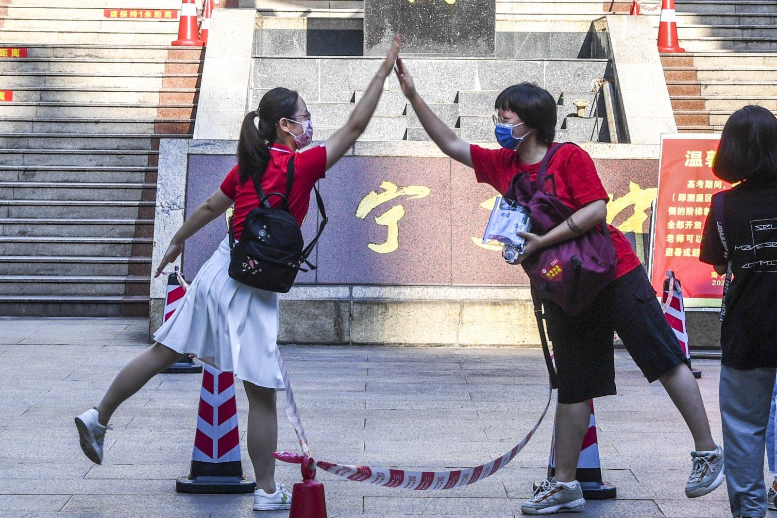 6月7日,在廣西南寧市第二中學新民校區考點,老師(左)與考生擊掌。新華社
