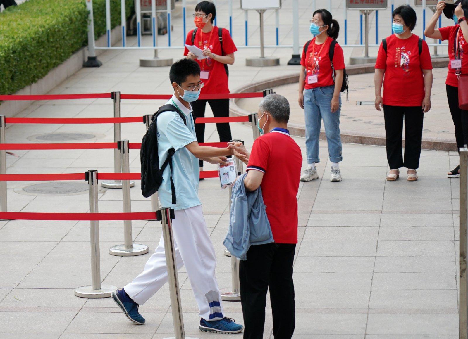 6月7日,在北京市中國人民大學附屬中學考點,考生在進考場前與老師擊掌。新華社