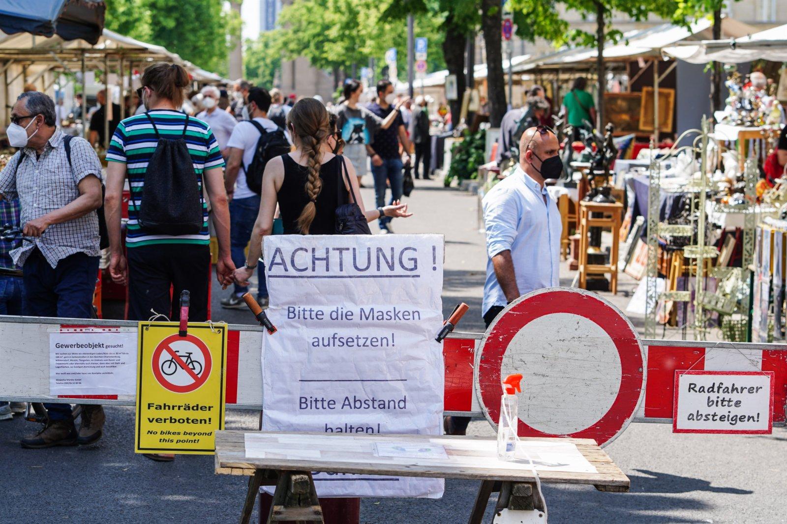 6月6日,德國首都柏林一處「跳蚤市場」入口的告示牌提示人們佩戴口罩並保持社交距離。(新華社)