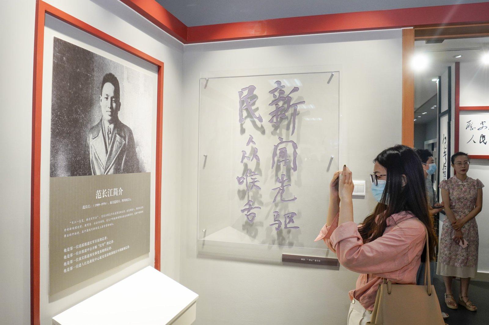 在「范長江與重慶」展覽館內,一名參觀者用手機拍攝展品。