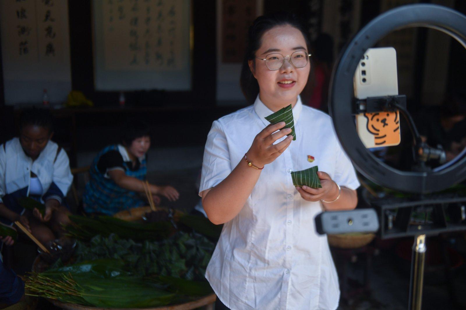 6月8日,湖源鄉的青年黨員志願者通過直播帶貨的形式為特色灰湯粽擴大知名度。(新華社)