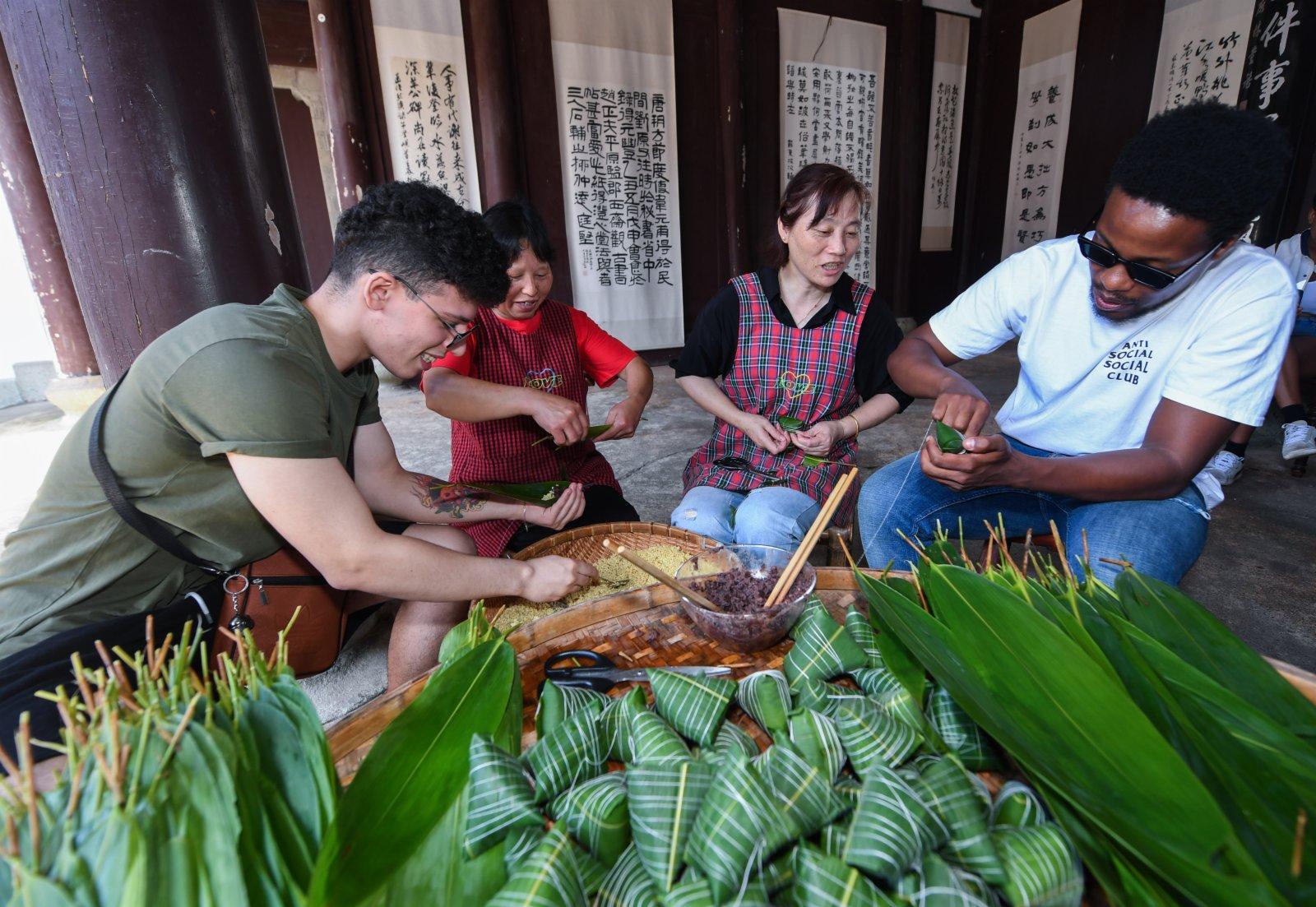 6月8日,湖源鄉窈口村村民帶着前來旅遊的浙江科技學院留學生體驗傳統灰湯粽的製作,感受端午傳統文化的魅力。(新華社)