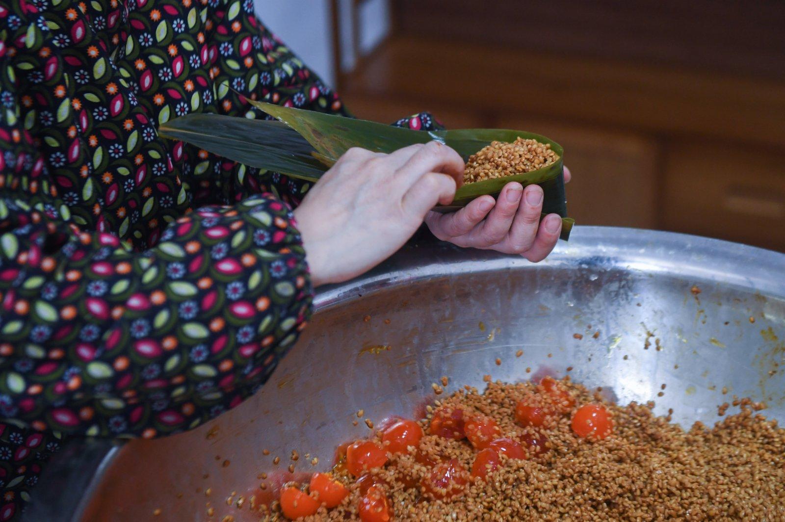 6月8日,湖源鄉窈口村村民在製作不同口味的灰湯粽,作為端午節特色旅遊商品銷售給遊客。(新華社)