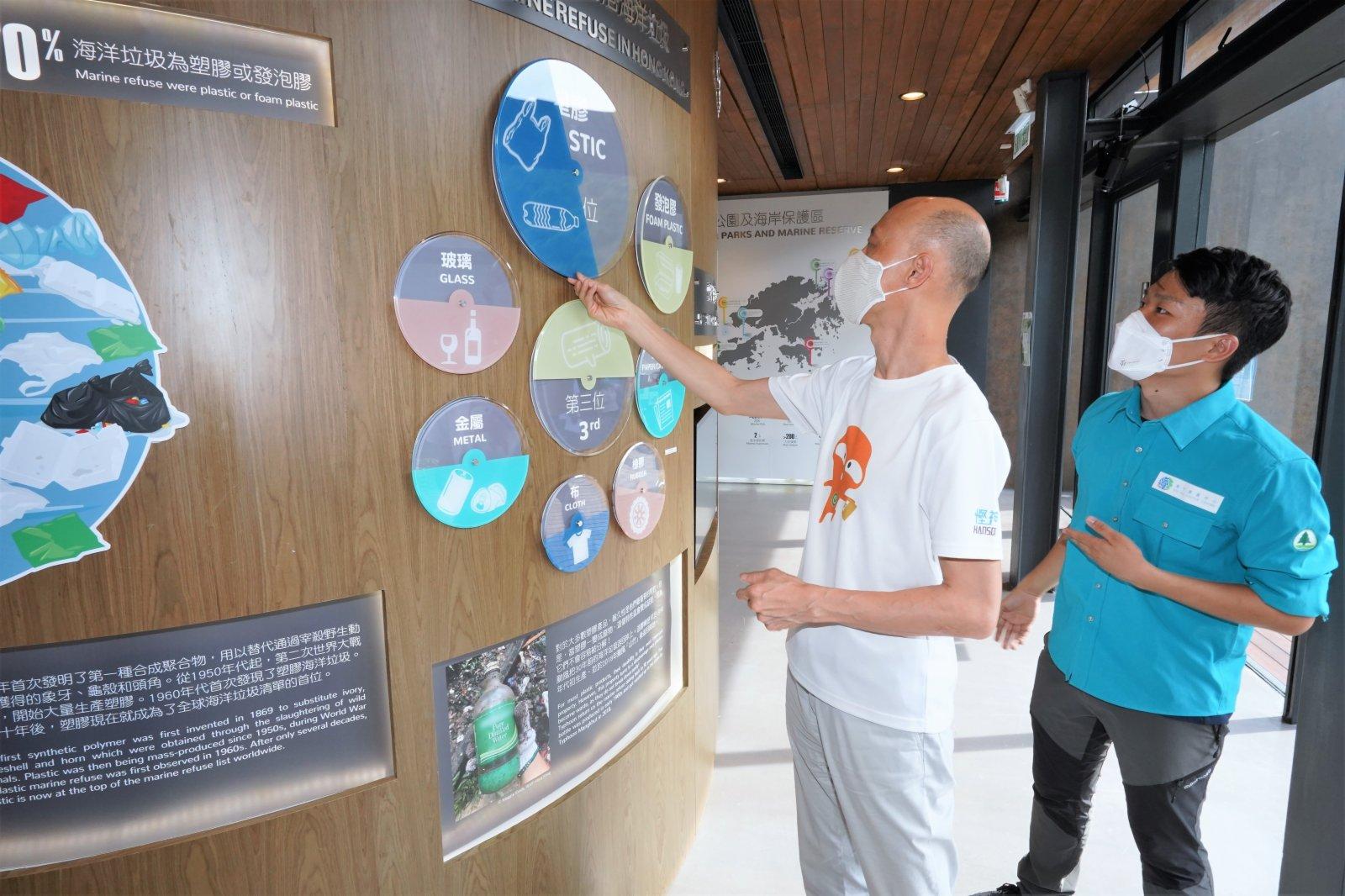環境局局長黃錦星(左)參觀中心的展覽廳。展品介紹海岸公園的管理及保育措施、海洋生態、海下歷史及海洋面對的威脅等教育資訊。(政府新聞處)