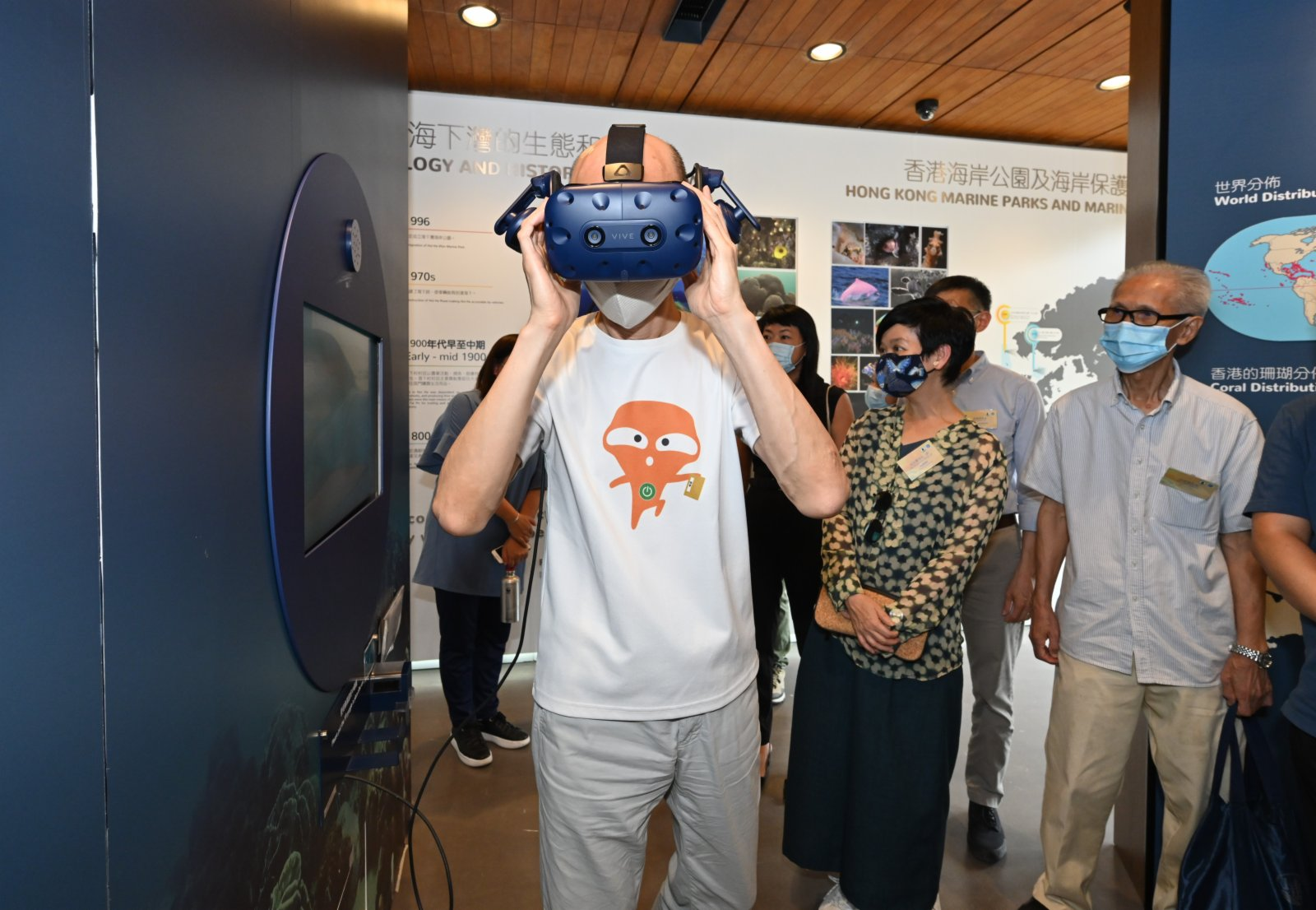 環境局局長黃錦星(左)以虛擬實景(即VR)技術製作的互動式展覽「向海底出發」,一試「潛」入海岸公園的海底世界。(政府新聞處)