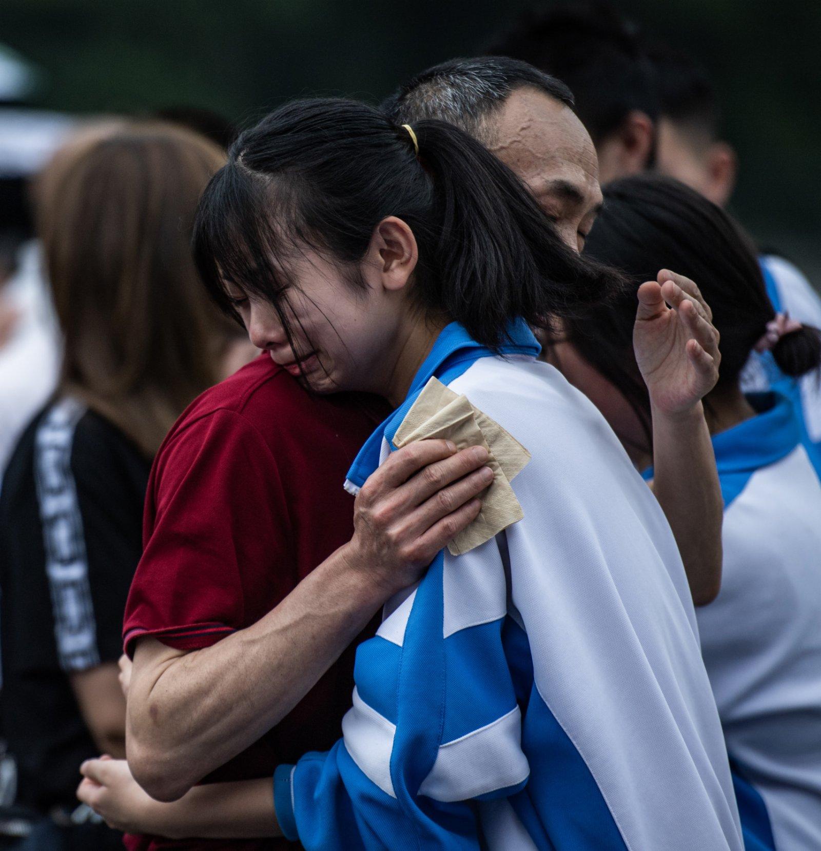 9日,烏當中學高三學生和家長在成人儀式上擁抱。
