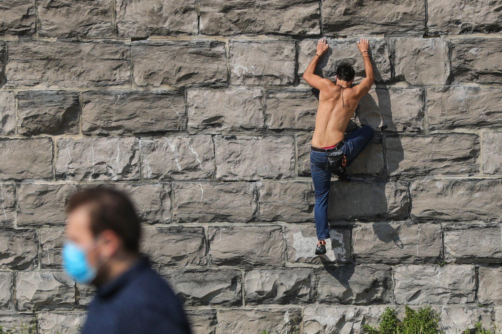 6月9日,在比利時布魯塞爾的五十周年紀念公園,一名男子練習攀巖。(新華社)