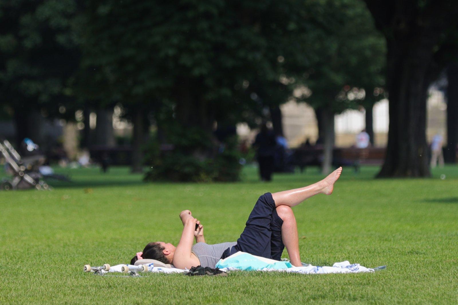 6月9日,一名女子在比利時布魯塞爾的公園休閒。(新華社)