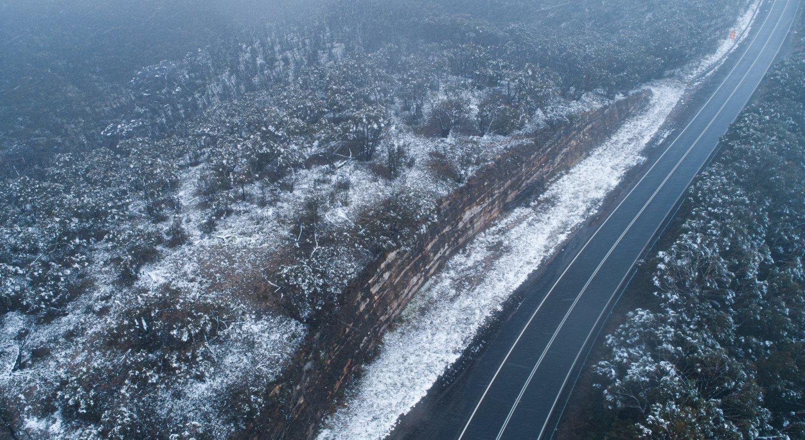 這是6月10日在澳大利亞新南威爾士州藍山地區拍攝的一條雪後公路(無人機照片)。(新華社)