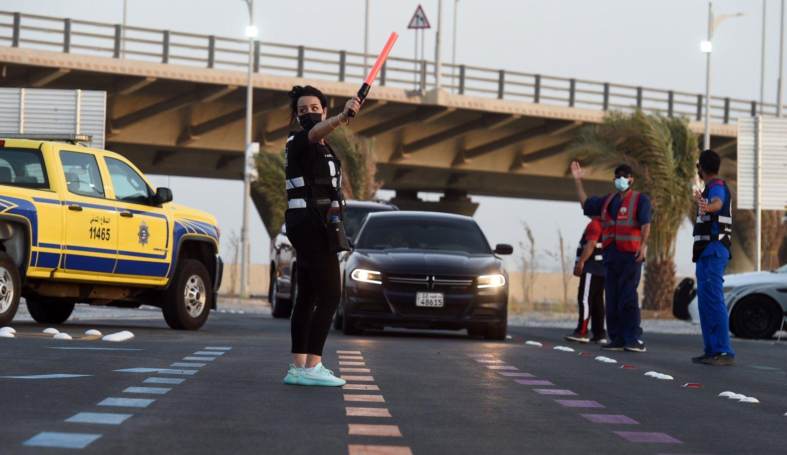 6月10日,工作人員在科威特首都科威特城的「免下車」新冠疫苗接種中心指揮車輛。(新華社)