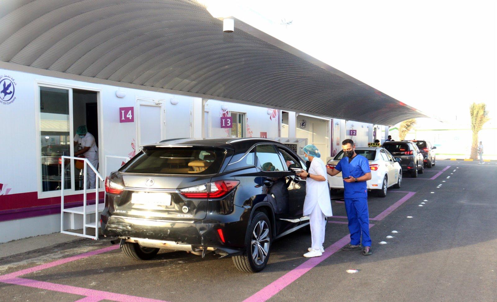 6月10日,在科威特首都科威特城的「免下車」新冠疫苗接種中心,醫務人員準備為車內人員接種新冠疫苗。(新華社)
