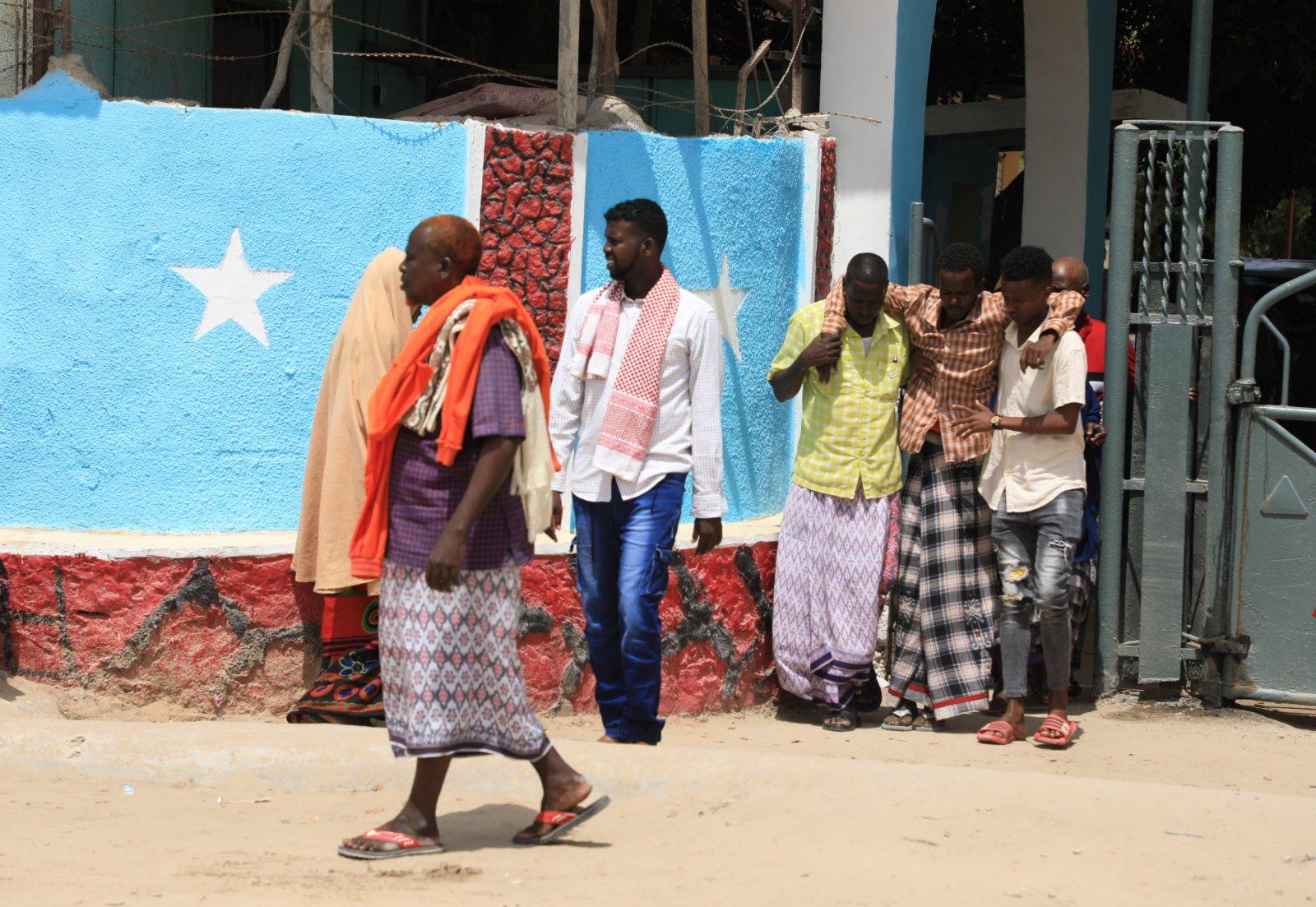 6月15日,一名傷員在人們的攙扶下走出索馬里首都摩加迪沙的一所醫院。(新華社)