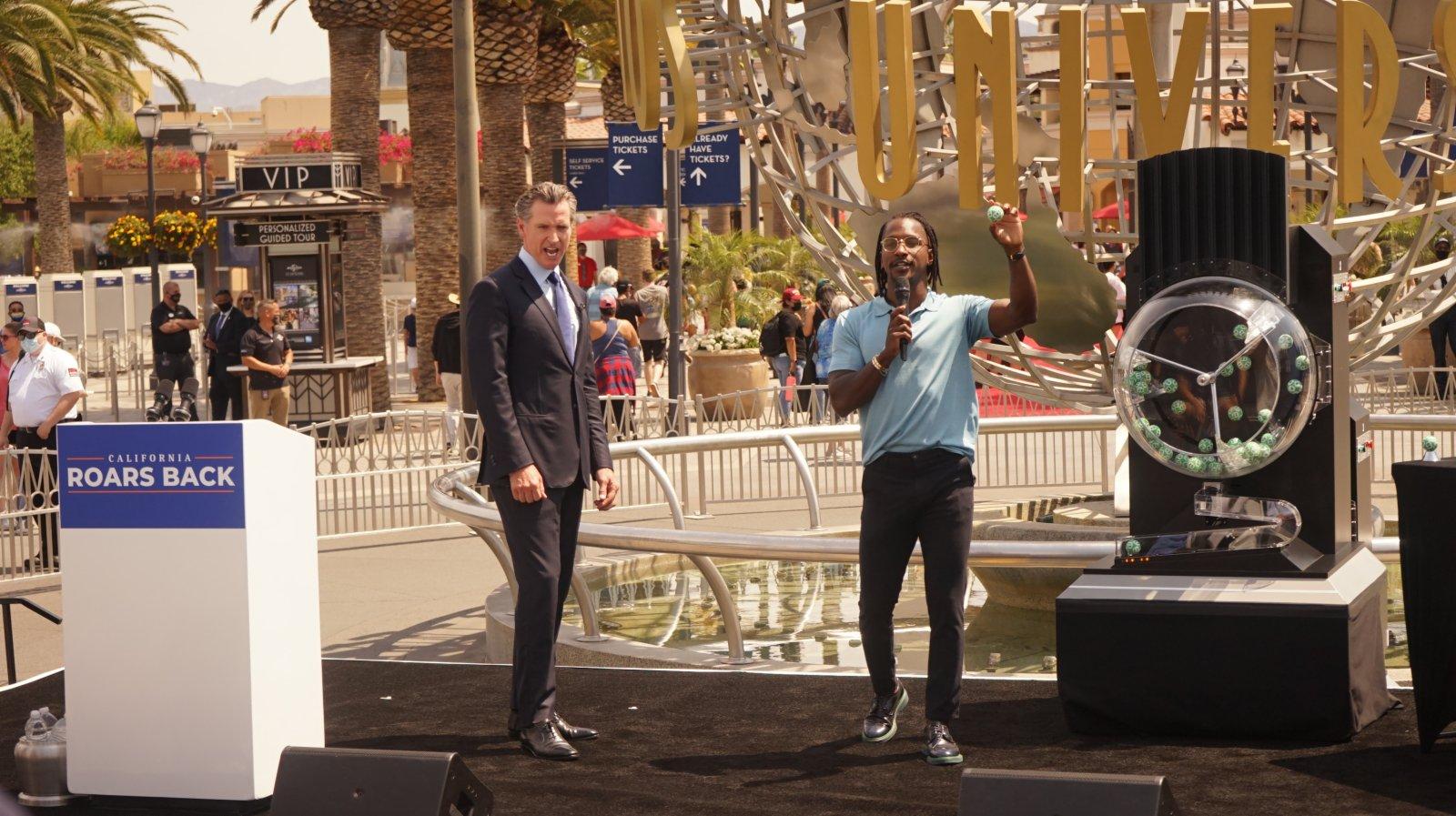 6月15日,美國加利福尼亞州州長紐瑟姆(左)在洛杉磯好萊塢環球影城宣布經濟全面重啟,並參加打新冠疫苗抽獎活動。(新華社)