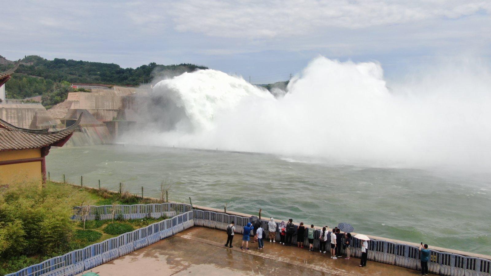 6月19日,遊客在黃河小浪底水利樞紐工程出水口觀看調水調沙場景。(新華社)