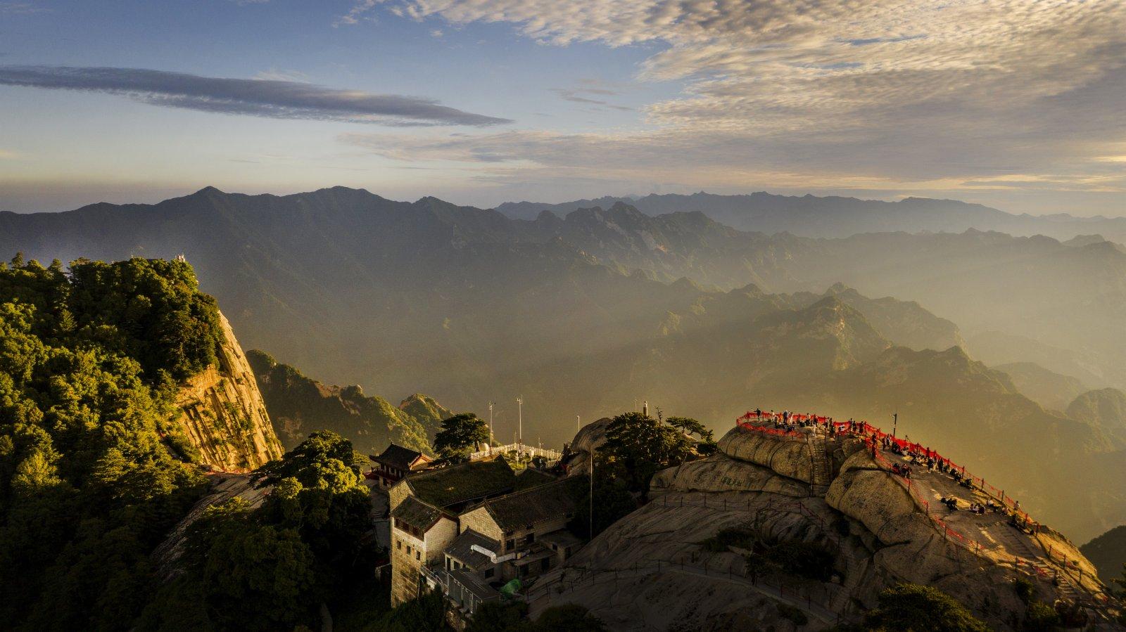 6月19日,遊人在華山西峰觀賞夕陽(無人機照片)。(新華社)