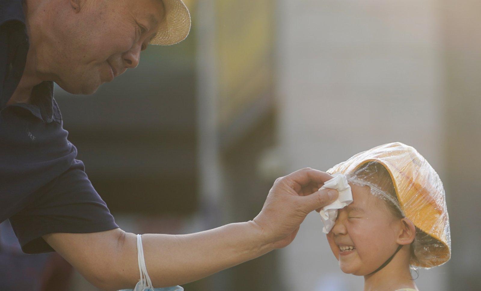 6月20日,在北京華熙LIVE·五棵松商業街區一處噴泉旁,家長擦乾小朋友臉上的水。(新華社)