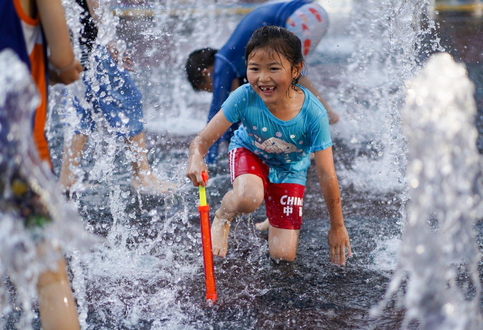 6月20日,孩子們在北京華熙LIVE·五棵松商業街區一處噴泉戲水。(新華社)