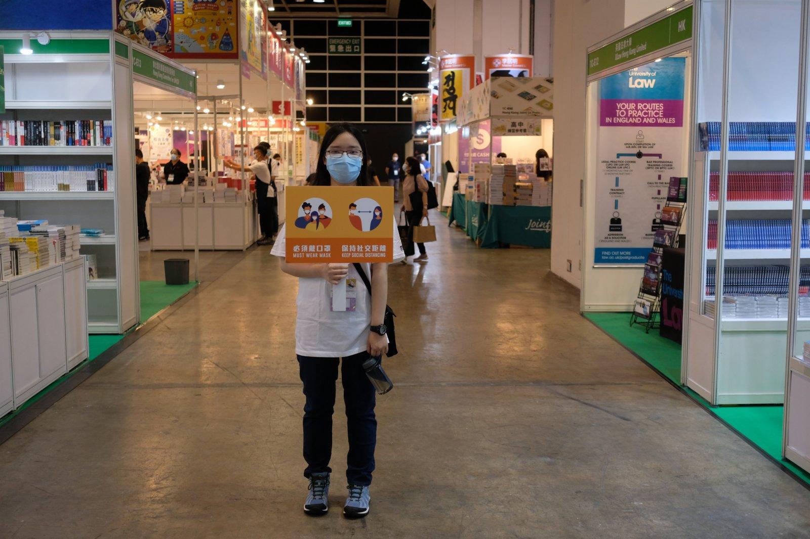 工作人員手持寫有「必須戴口罩、保持社交距離」標語的牌子,呼籲參展市民做好防疫措施。(記者麥鈞傑攝)