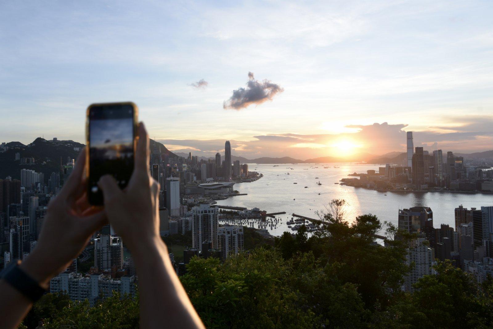 圖為市民用手機拍攝日落。(中新社)