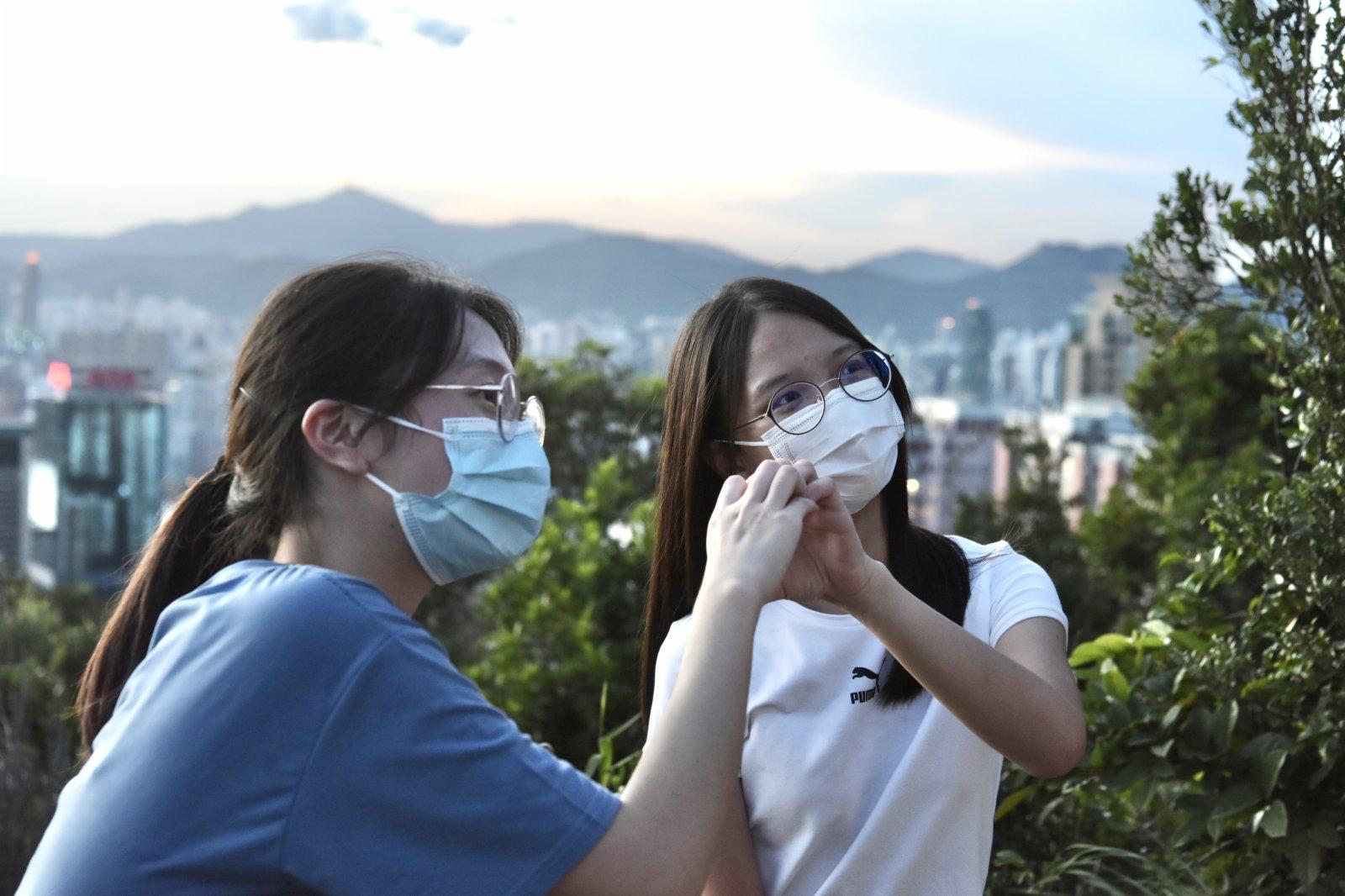 圖為香港市民觀看日落時擺出心形手勢。(中新社)
