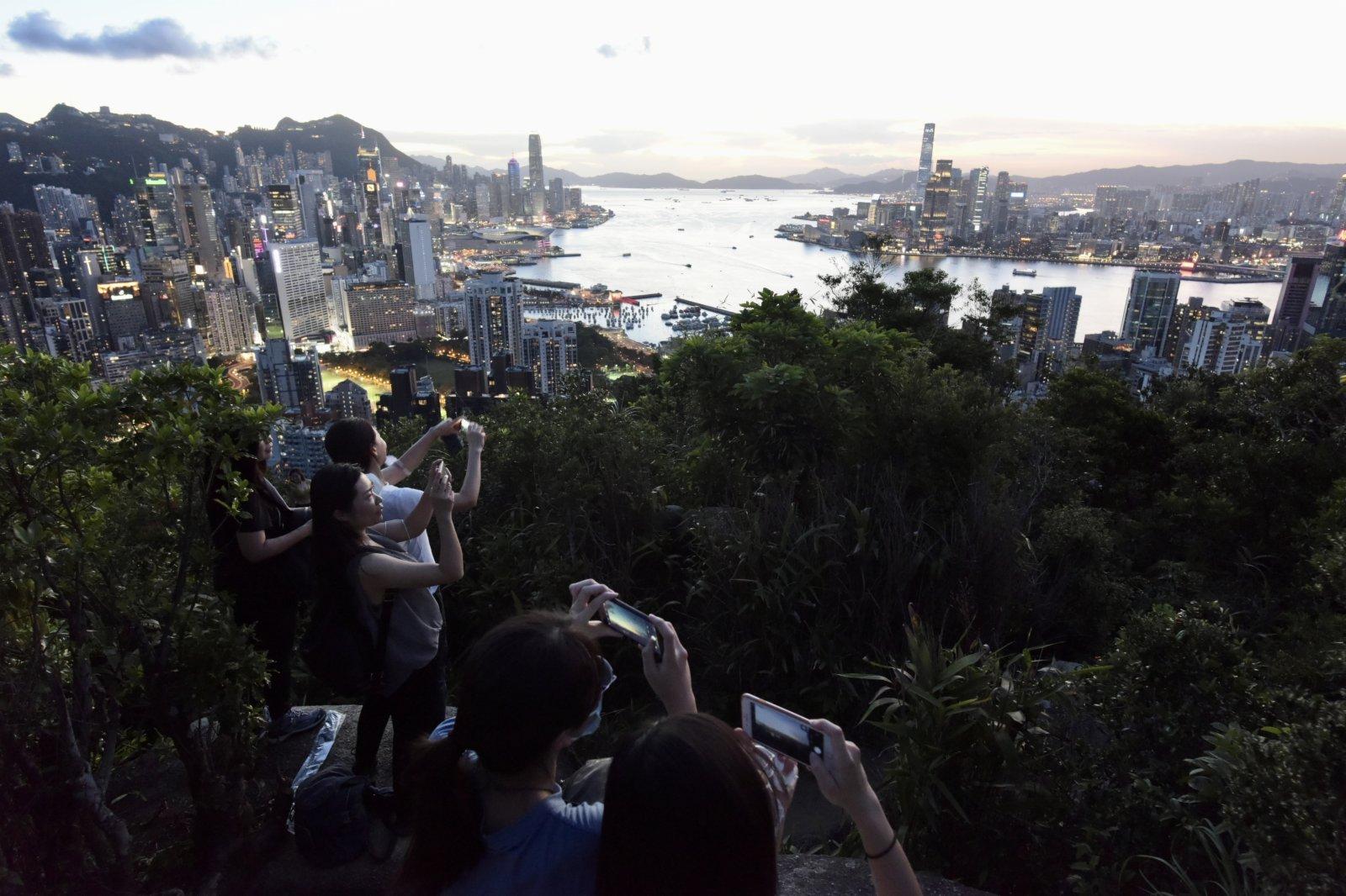 圖為市民舉起手機拍攝晚霞。(中新社)