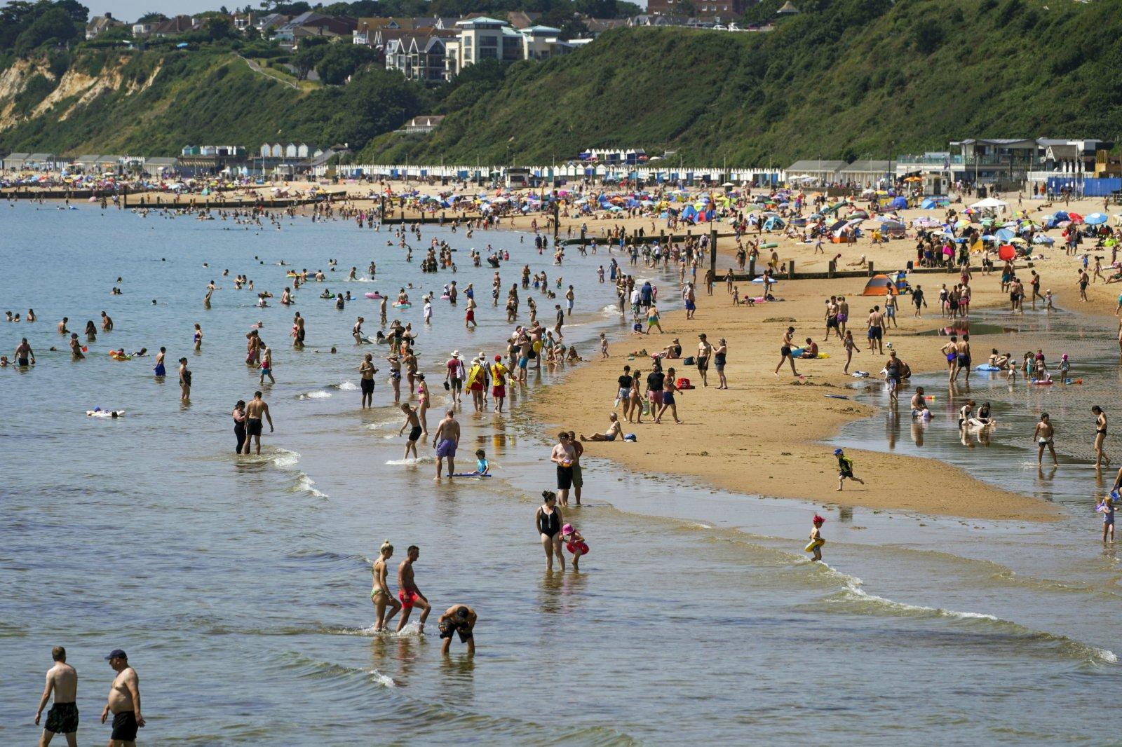 人們聚集在英格蘭多塞特郡的伯恩茅斯海灘。(美聯社)