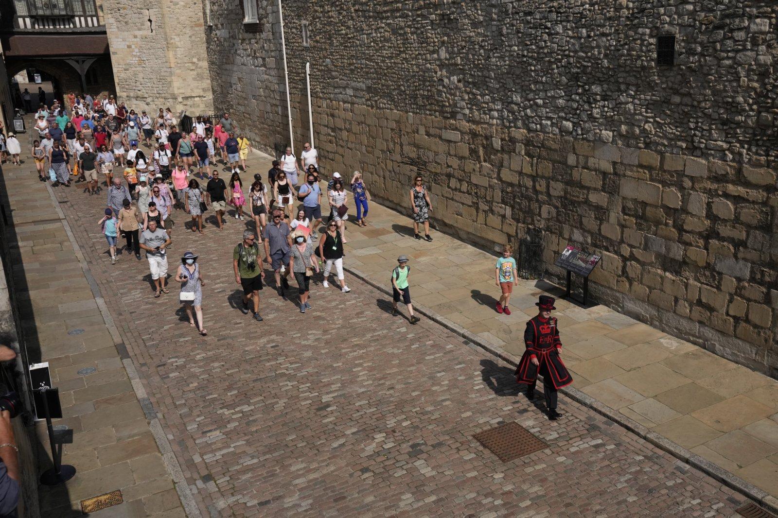 圖為嚮導帶領遊客參觀倫敦塔。(美聯社)