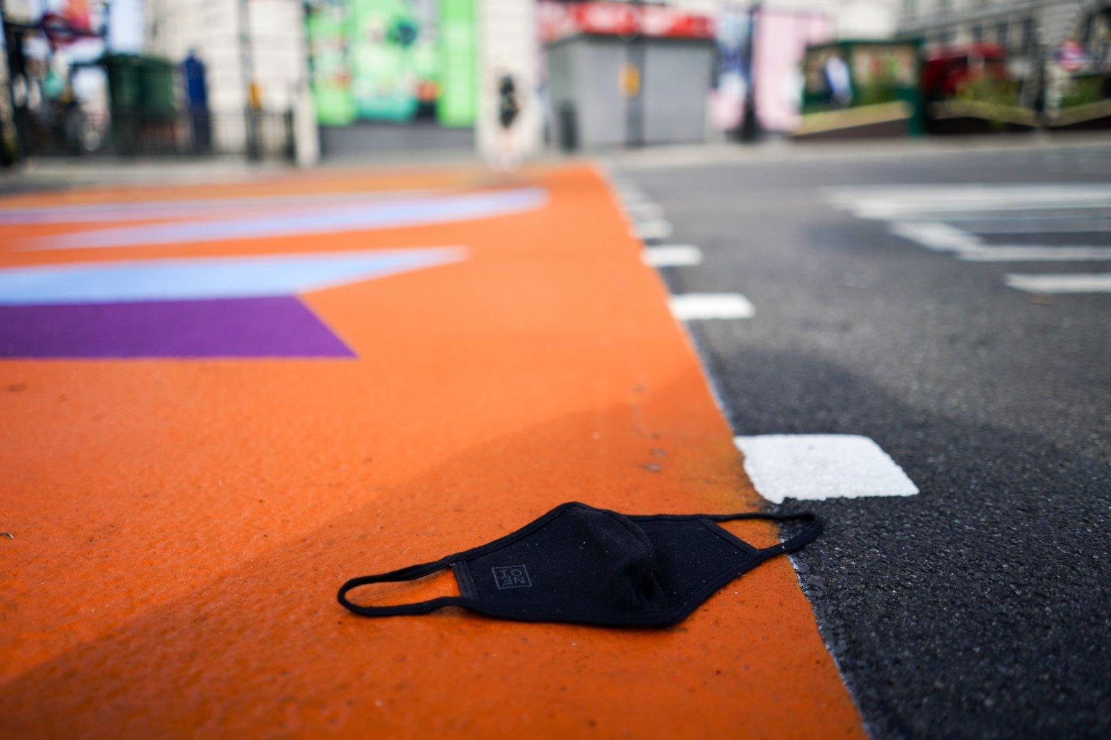 圖為倫敦市中心皮卡迪利廣場的地面上有一個口罩。從19日開始,英國法律不再要求民眾戴口罩。(美聯社)