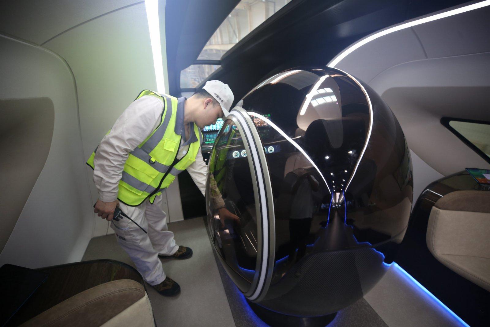 圖為技術人員在列車駕駛室進行設備操作演示。