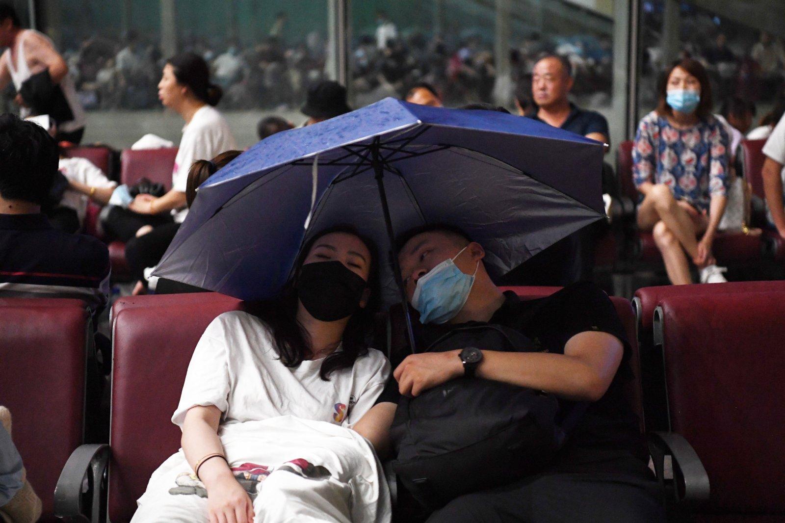 7月20日,旅客滯留在鄭州東站。候車廳出現漏雨情況,旅客撐傘擋雨。(新華社)