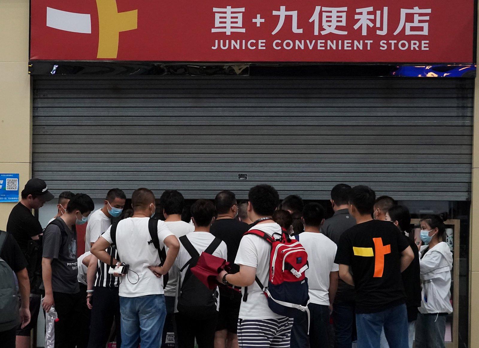 7月20日,滯留旅客在鄭州東站一家便利店外排隊購物。(新華社)